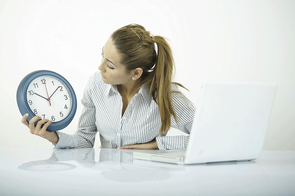 Frau blickt auf Uhr am Schreibtisch – es ist zehn nach zehn